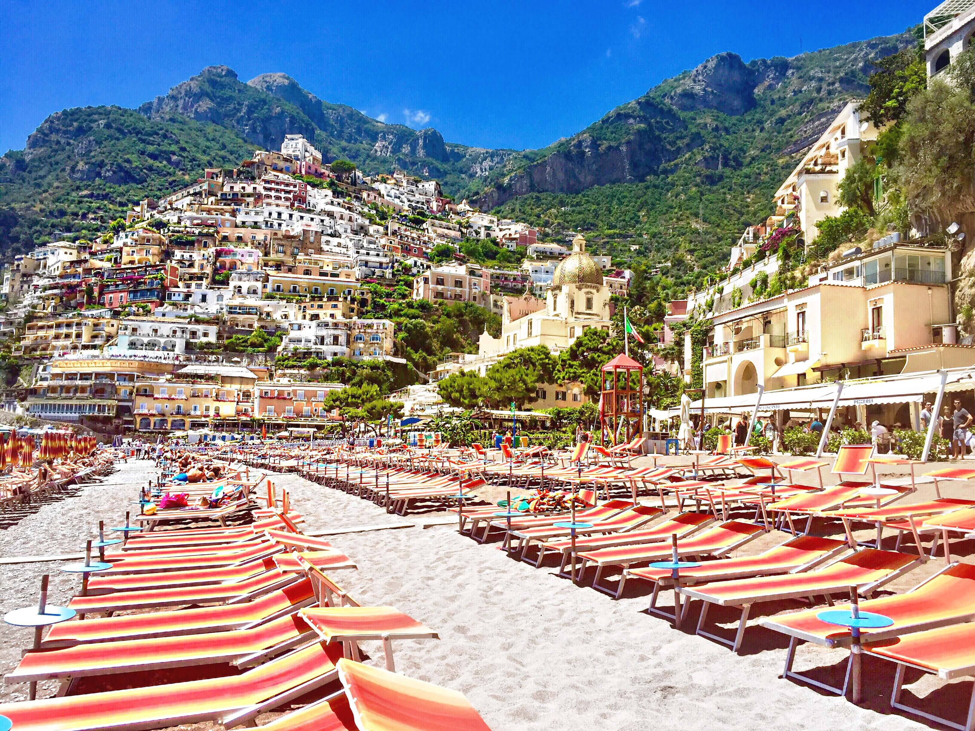 Orange lounges lined up on the beach in Positano
