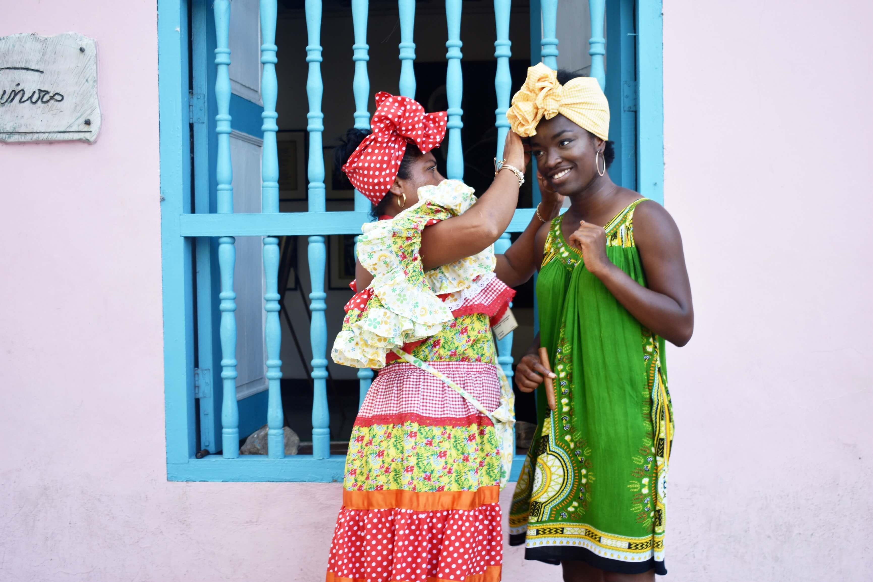 A colorfully-dressed woman puts on a scarf for me in Havana
