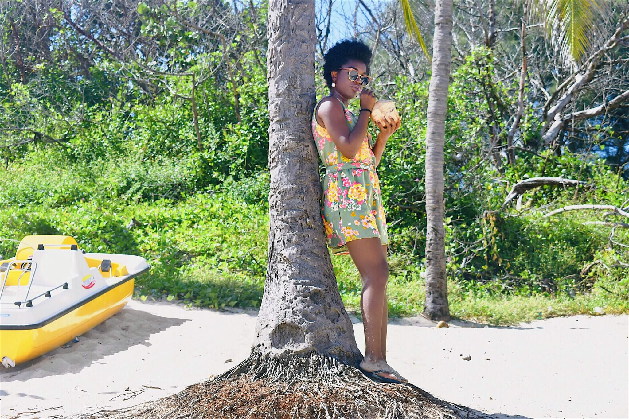Somto sipping a fresh coconut under a tree at Playa del Este