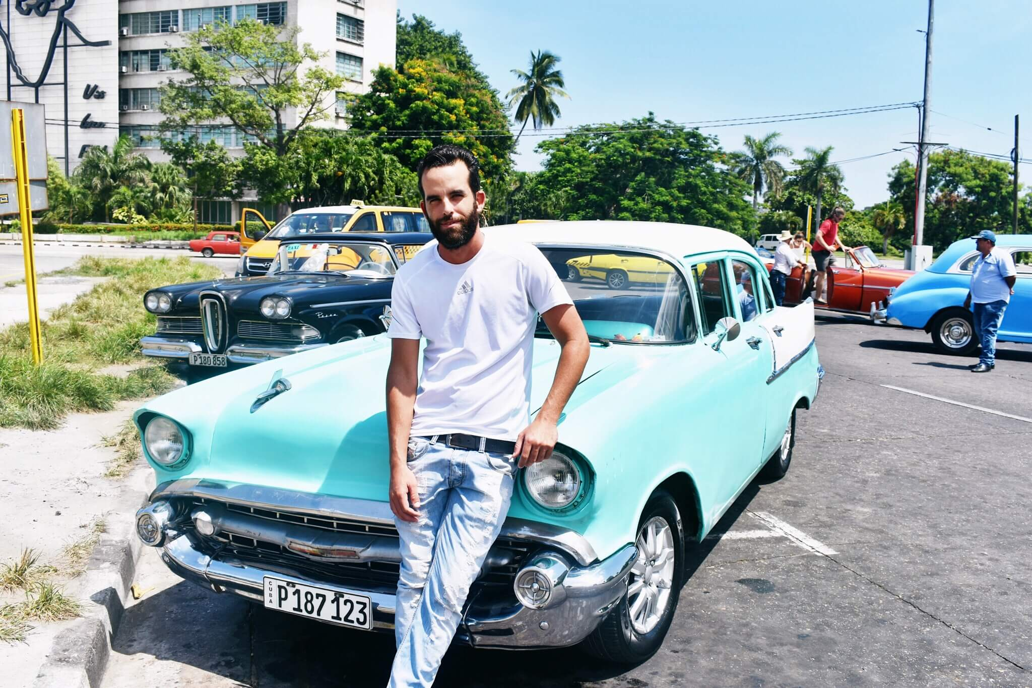 Alejandro standing in front of his classic car at Plaza de la Revolucion
