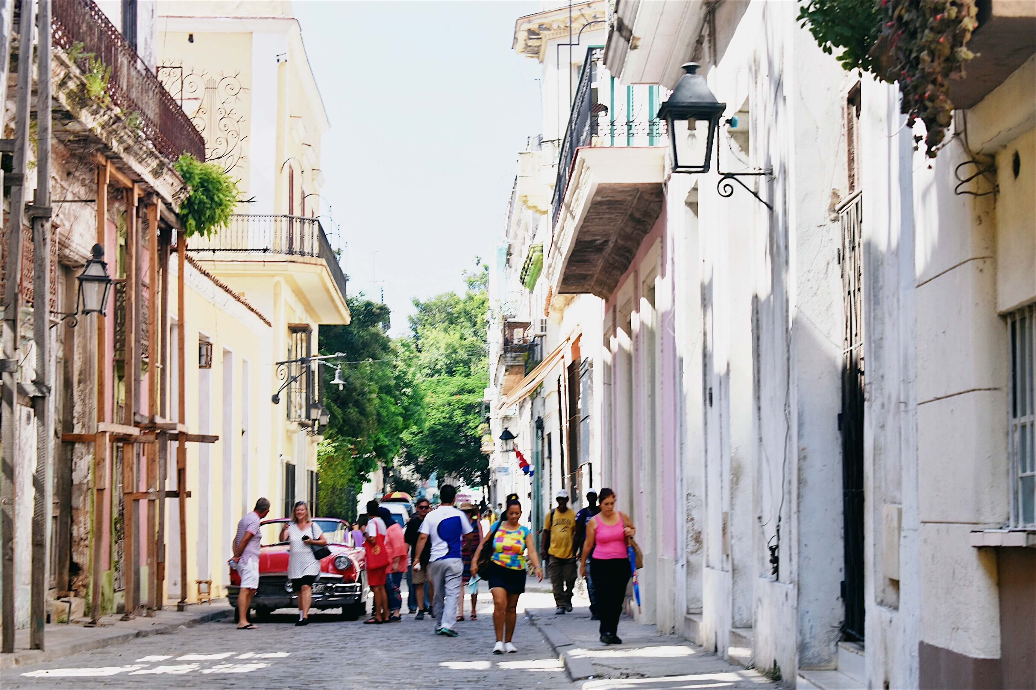 Pedestrians walking through the colorful streets of Havana Vieja