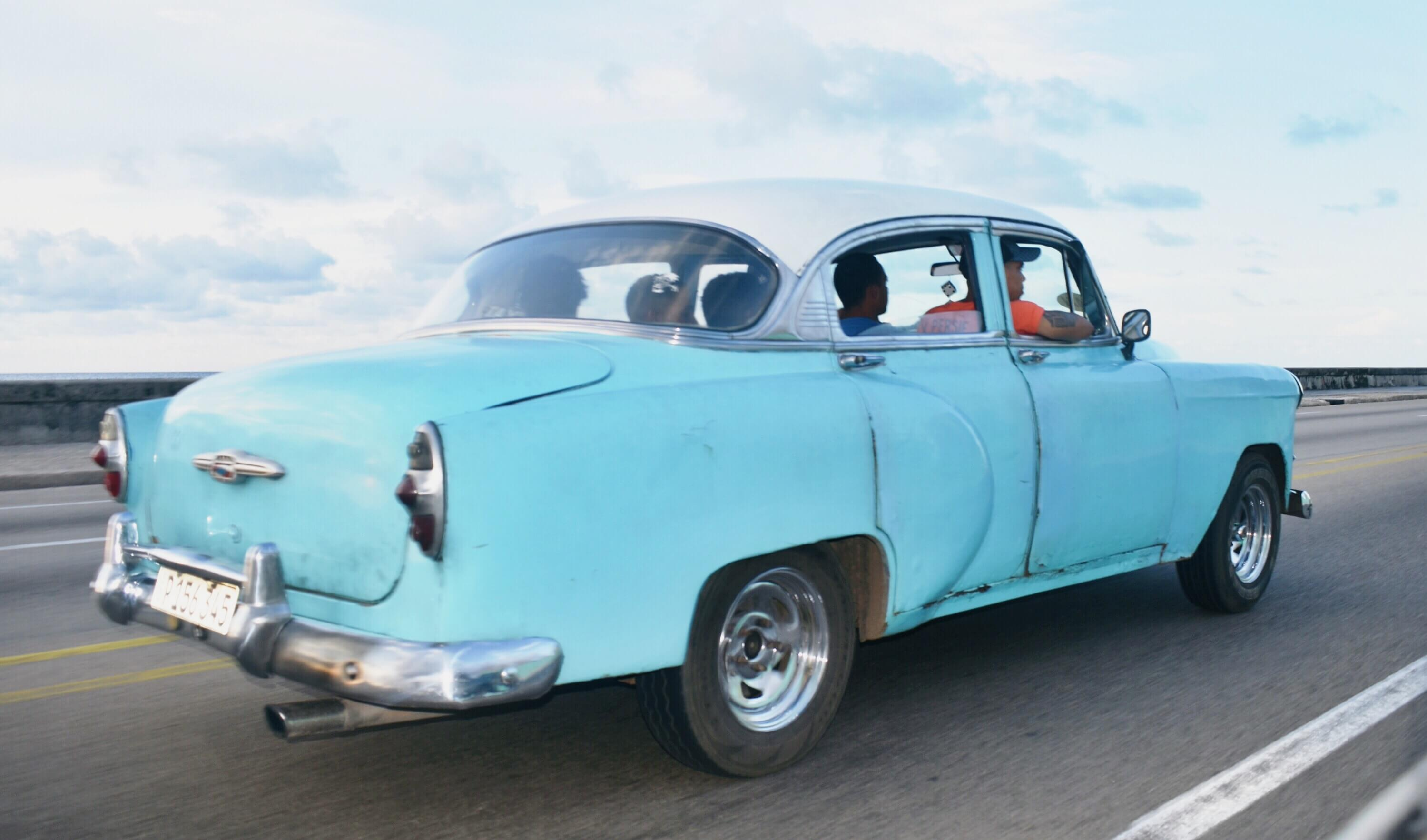 A blue classic car zips through Havana's El Malecon strip