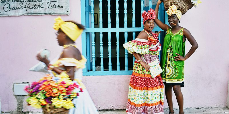 A colorfully-dressed Habanera walks past as Laza and I take photos
