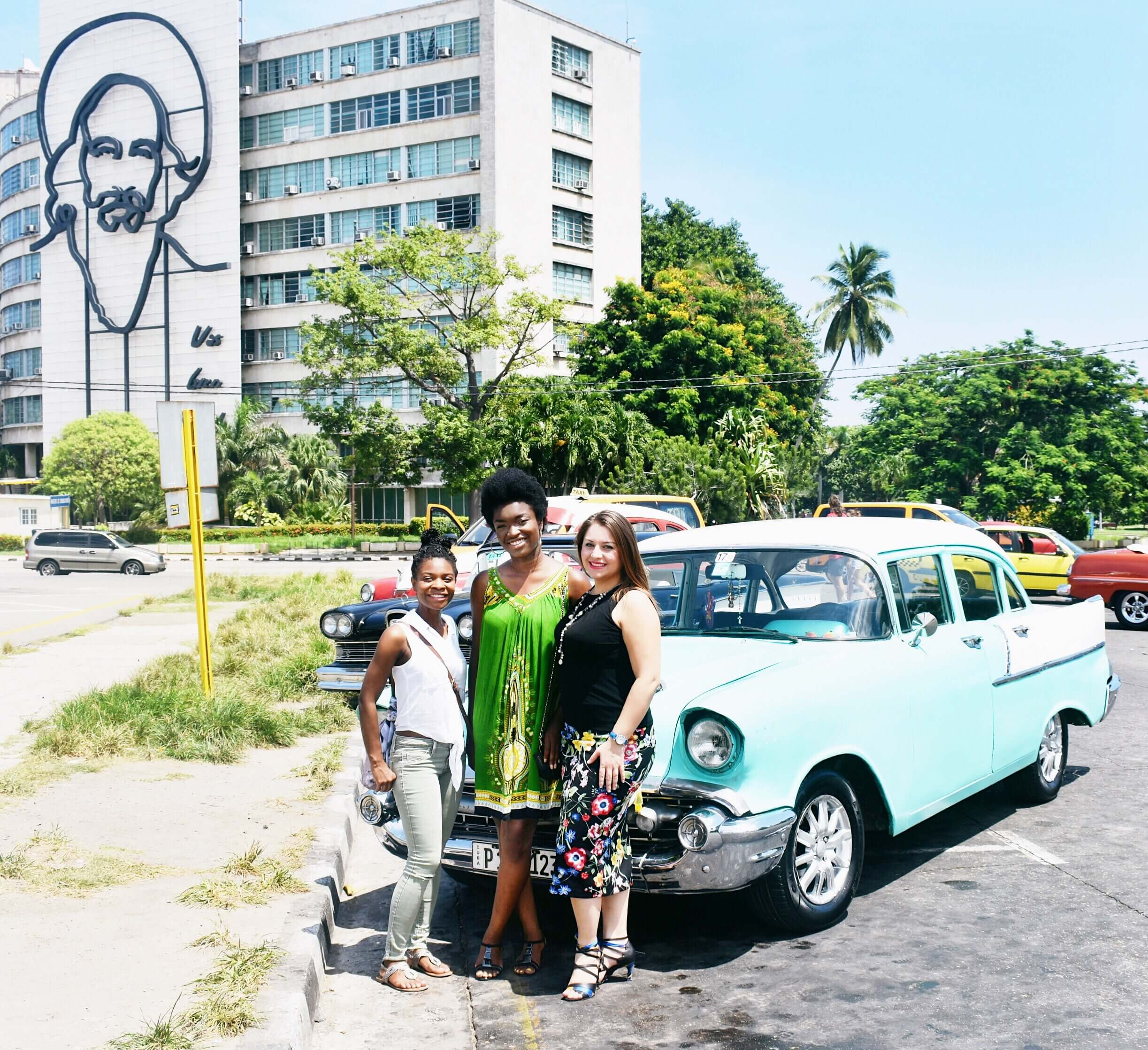 The girls and I posing in front of our ride at Plaza de la Revolucion