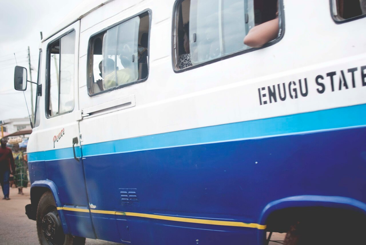 A blue and white bus zips through the streets of Enugu