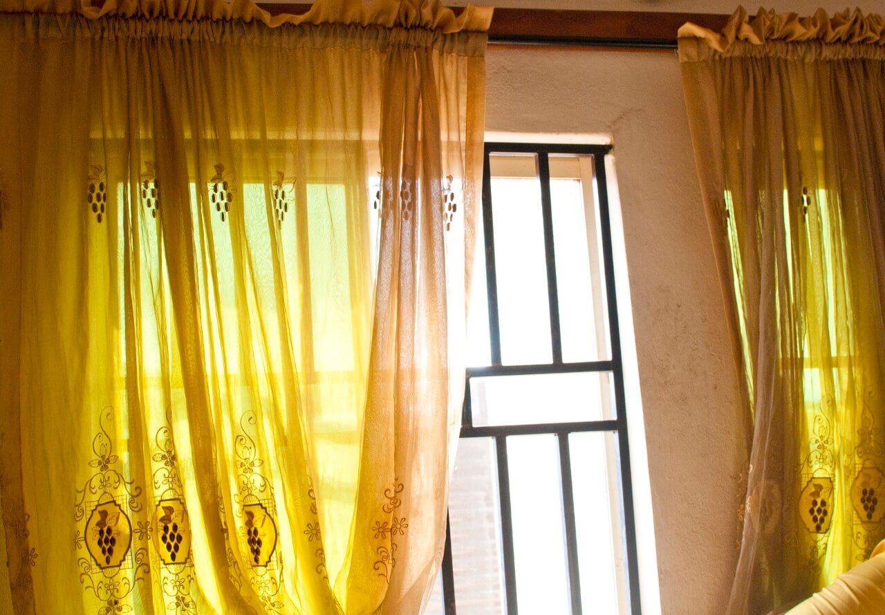 Yellow curtains covering the window at our house in Enugu