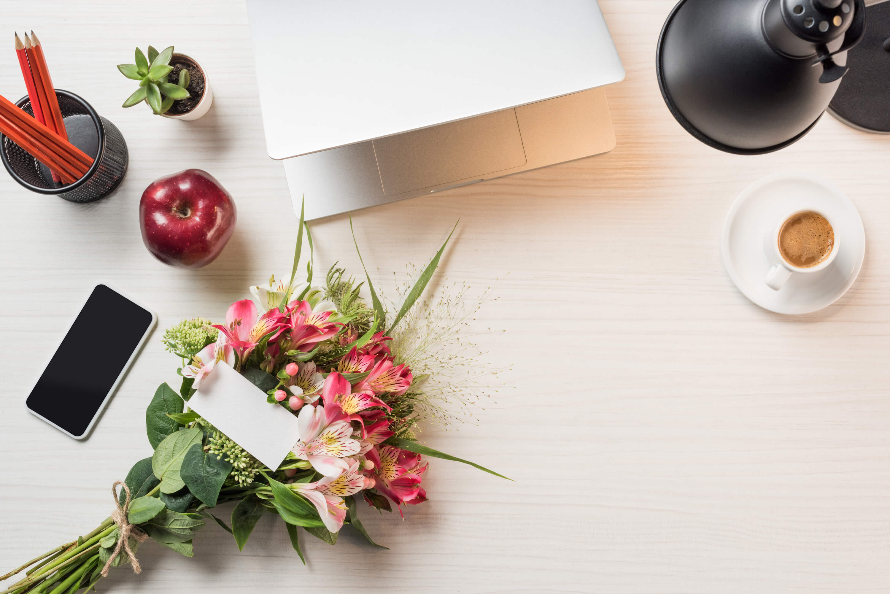 How to build an email list for your travel blog - flowers and apple on desk