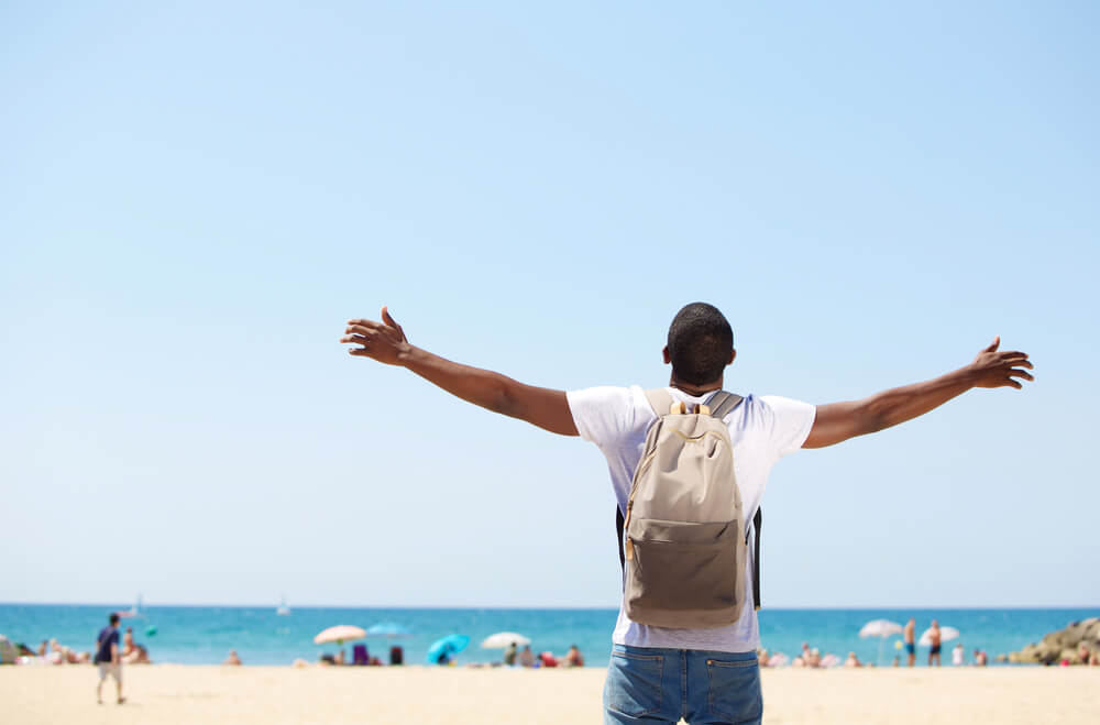 Traveling to normalize blackness - black man at the beach
